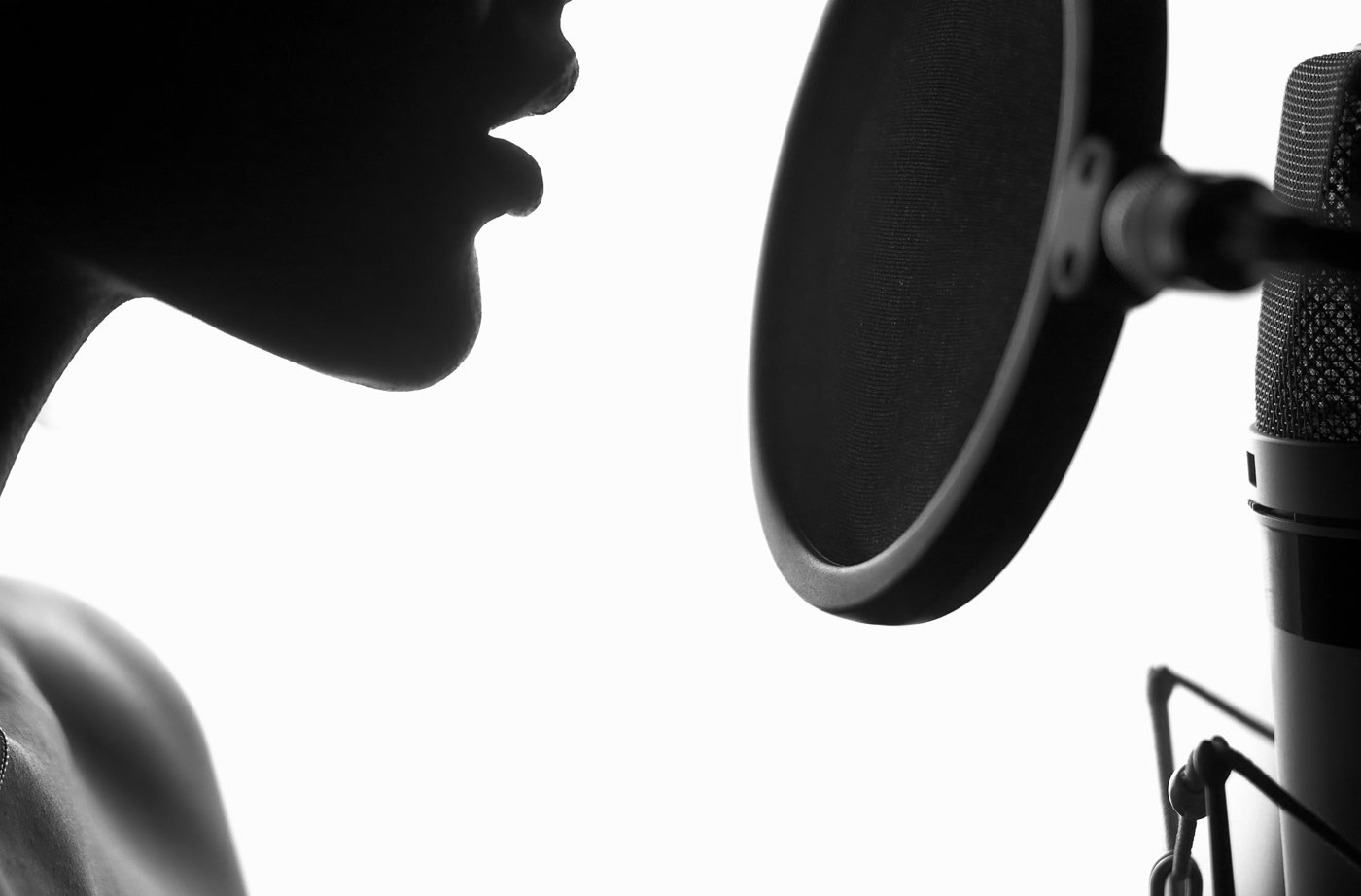 Portrait of young woman recording a song in a professional studio. Black and White.